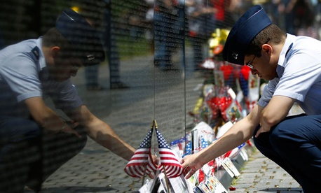 A visitor looks at items left at the Vietnam Veterans Memorial, ahead of Memorial Day in Washington, Sunday, May 26, 2013.