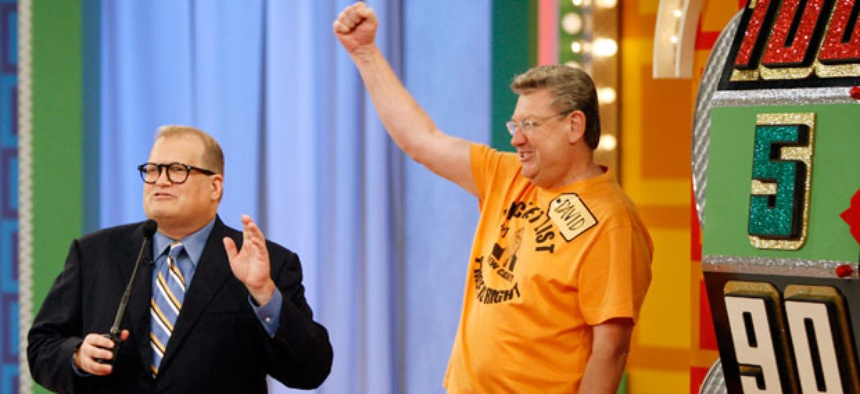 """A contestant stands next to the """"Big Wheel"""" during a taping of the Price is Right. When mail carrier Cathy Wrench Cashwell appeared on the same show, officials discovered she was more mobile than her workers compensation claims suggested."""