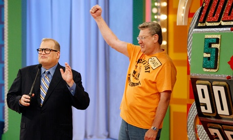 "A contestant stands next to the ""Big Wheel"" during a taping of the Price is Right. When mail carrier Cathy Wrench Cashwell appeared on the same show, officials discovered she was more mobile than her workers compensation claims suggested."