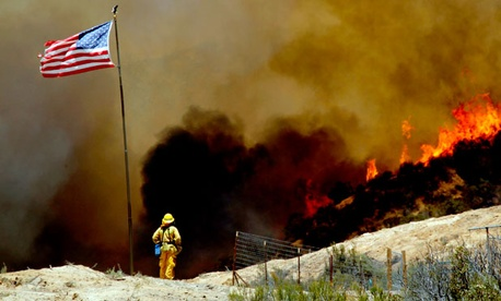 A firefighter watches a wildfire northeast of Castaic, Calif., in May.