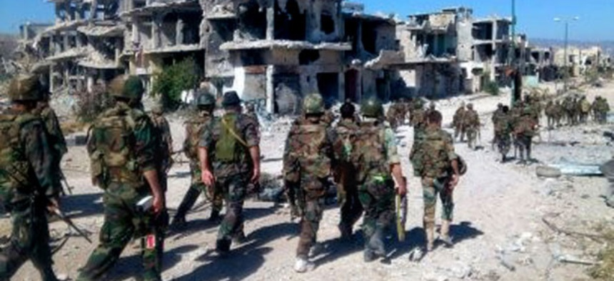 Syrian soldiers loyal to President Bashar Assad in the town of Qusair patrol in early June.