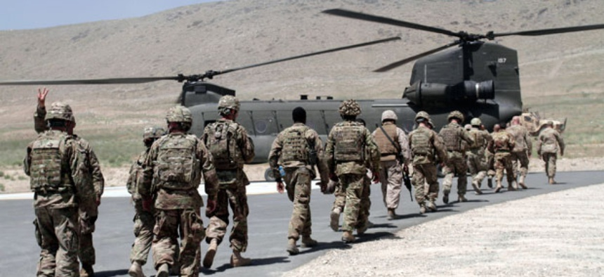 NATO soldiers walk towards a Chinook helicopter after a ceremony at a military academy on the outskirts of Kabul, Afghanistan.