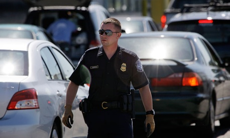 A Customs and Border Protection officer walks through a line of cars at a crossing from Canada near Blaine, Wash.