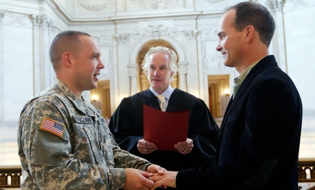 Army Capt. Michael Potoczniak, left, and Todd Saunders are married by deputy marriage commissioner John Loschmann at San Francisco City Hall.