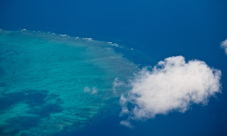 The Great Barrier Reef is visible from high above the water's surface.