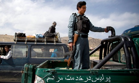 An Afghan police officer stands guard at a checkpoint on a road leading to Narkh district on the outskirts of Maidan Shahr, Afghanistan