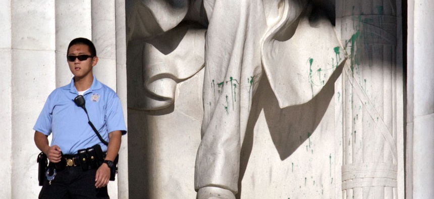 A U.S. Park Police officer stands guard next to the statue of Abraham Lincoln after it had been vandalized.