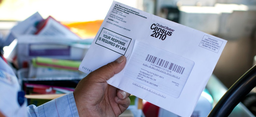 A Postal Service employee holds a 2010 census form.