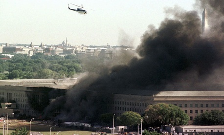 A helicopter flies over the burning Pentagon Tuesday, Sept. 11, 2001.