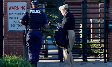 A member of the Navy has her identification checked Tuesday as she attempts to enter Washington, DC's Naval Yard the day after the shooting.