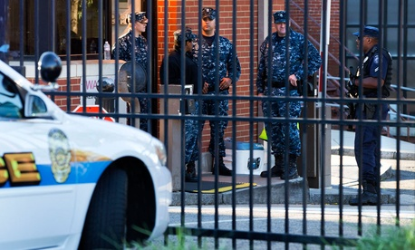 Naval officers  stand guard inside the gate of the closed Navy Yard Tuesday.