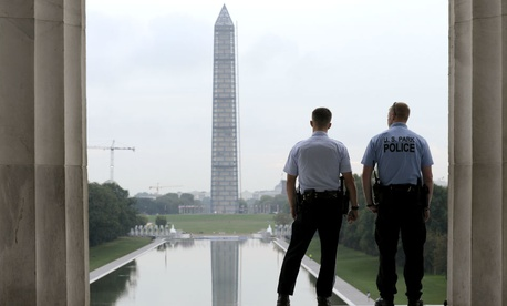 With the Washington Monument in the distance, Park Service police officers stand on duty at the Lincoln Memorial.