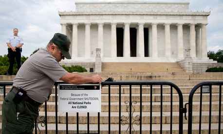 A Park Police officer watches as a National Park Service employee posts a sign on a barricade closing access to the Lincoln Memorial on Oct. 1, the day the government shutdown began.
