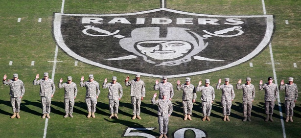 Servicemembers stand on the field before the game at the Oakland Coliseum Sunday.