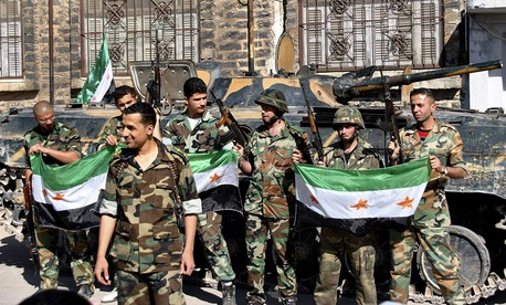 Syrian army soldiers hold the Syrian revolution flags in 2012.