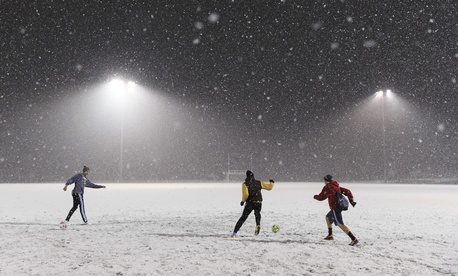 High schoolers play soccer in McLean, Va., while snow falls Thursday evening.