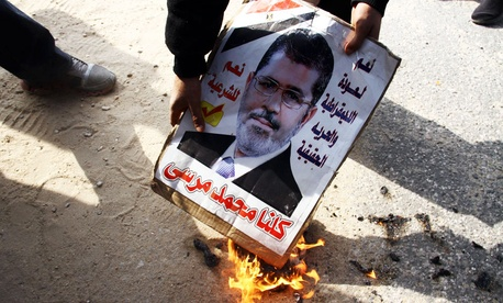 An opponent of Egypt's ousted President Mohammed Morsi burns a poster with his photo on it in Cairo, Egypt, Wednesday, Jan. 8, 2014.
