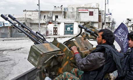 ree Syrian Army fighters sit behind their antiaircraft machine gun in Aleppo last year.
