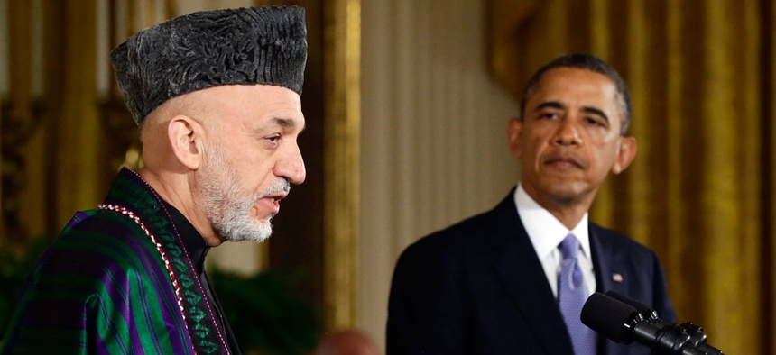 President Barack Obama listens as Afghan President Hamid Karzai speaks during a news conference.