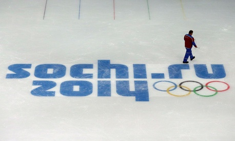 A worker leaves after painting the ice in the Iceberg Skating Palace in Sochi Saturday.