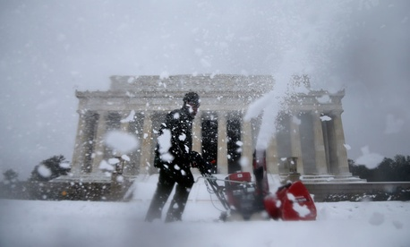A Park Service employee clears snow Thursday on the grounds of the Lincoln Memorial.