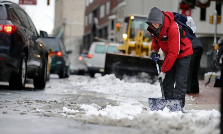 Workers clear newly-fallen snow from a street, Tuesday, Feb. 18, 2014, in Trenton, N.J.