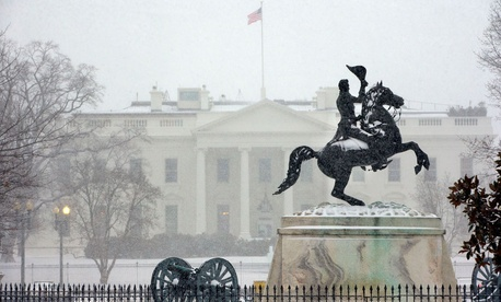 Snow falls on a statue of Andrew Jackson in Lafayette Park Monday.