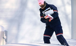 U.S. Postal Service letter carrier Jamie Jasmon struggles through snow while delivering the mail. The White House's budget plan for USPS includes a shift from to-the-door delivery.