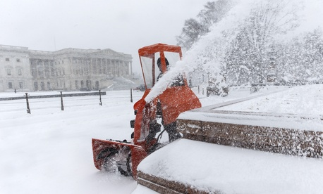 Workers clear snow Monday on Capitol Hill.