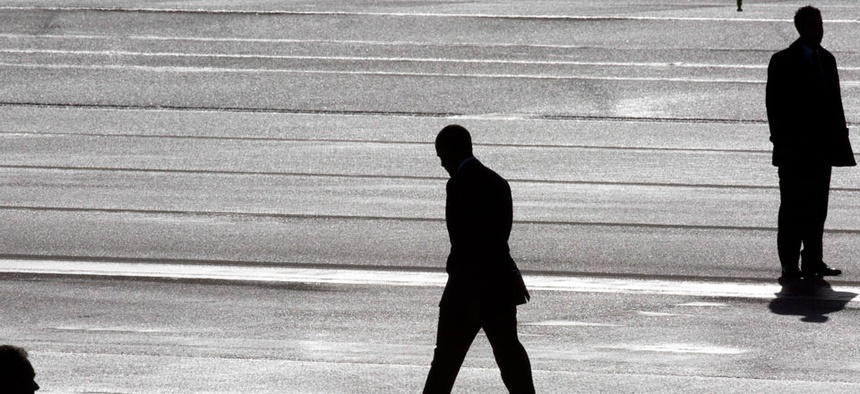 President Barack Obama, center, and two Secret Service agents are silhouetted as he walks towards Marine One helicopter upon arrival at Schiphol Amsterdam Airport Monday.