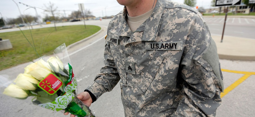 An unidentified soldier holds flowers dropped off at Fort Hood's main gate for shooting victims, Thursday, April 3, 2014.