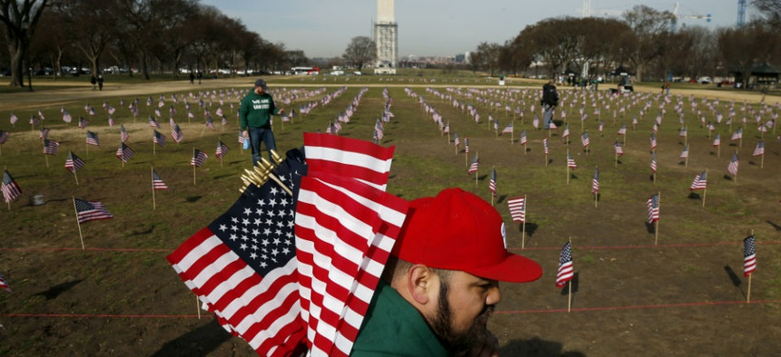 Army veteran Julio Bernal works with others from Iraq and Afghanistan Veterans of America to place 1,892 flags representing veteran and service members who have died by suicide to date in 2014 on the National Mall in Washington.