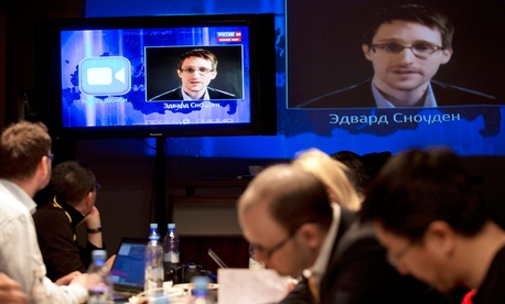 Edward Snowden, displayed on television screens, asks a question to Russian President Vladimir Putin during a nationally televised question-and-answer session, in Moscow.