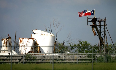 An American and Texas flag fly side by side Friday, May 31, 2013, in West, Texas, atop the destroyed remains of the fertilizer plant that exploded killing 15 and injuring 200.