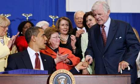 President Barack Obama hands Sen. Edward Kennedy, D-Mass., the first pen as he signs the Edward M. Kennedy Serve America Act, Tuesday, April 21, 2009.