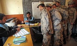 Afghan security personnel line up for the registration process before they cast their votes at a polling station in Kabul, Afghanistan, Saturday, April 5, 2014.