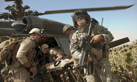 US Army flight medic SPC. Daniel Miller, right, stands guard as United States Marines place a colleague wounded in an IED strike into a waiting U.S. Army medevac helicopter.
