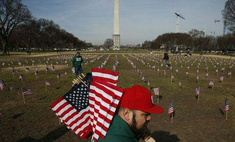 Army veteran Julio Bernal, works with others from Iraq and Afghanistan Veterans of America to place 1,892 flags representing veteran and service members who have died by suicide to date in 2014 on the National Mall.