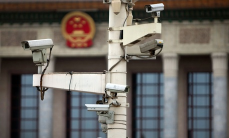 Surveillance cameras are set up at a lamp post against a China national emblem at Tiananmen Square in Beijing, China.