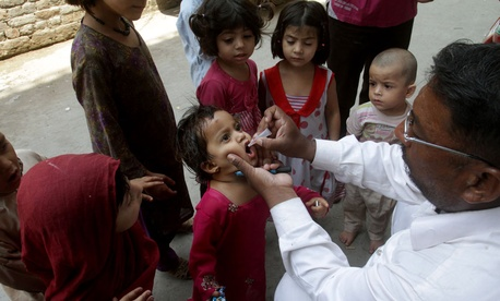 A Pakistani health worker gives an oral polio vaccine to a child in Lahore, Pakistan.