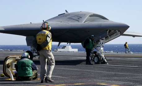 Flight deck crew prepare to launch the Navy experimental unmanned aircraft, the X-47B, aboard the nuclear powered aircraft carrier USS Theodore Rosevelt.