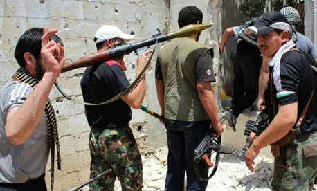 Syrian rebels hold their weapons as they prepare to fight against Syrian troops, in Homs province, Syria.