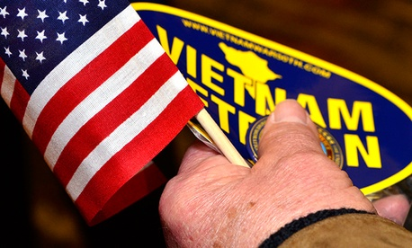 A veteran holds a sticker and a flag at a VA event in South Carolina in February.