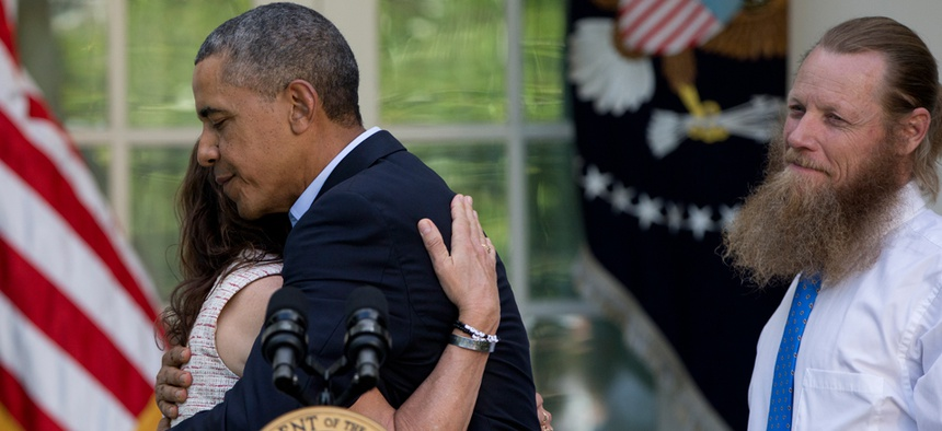 Obama hugs Jani Bergdahl, as Bob Bergdahl stands nearby on May 31.