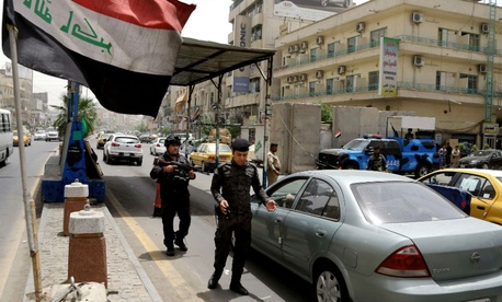 Iraqi federal policemen stand guard at a checkpoint in Baghdad, Iraq, Wednesday, June. 11, 2014.