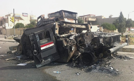 An Iraqi army armored vehicle is seen burned on a street of the northern city of Mosul Thursday.