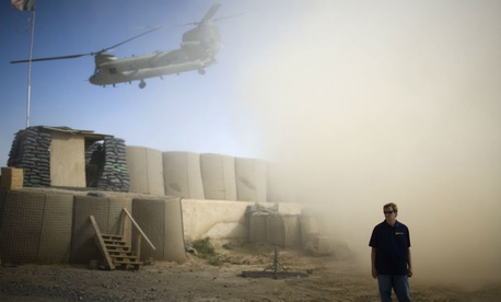 A U.S. contractor looks away from a dust cloud whipped up by a helicopter departing over the gatepost at Combat Outpost Terra Nova in Kandahar, Afghanistan.