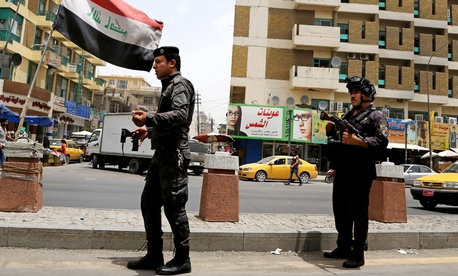 Iraqi federal policemen stand guard at a checkpoint in Baghdad Wednesday.