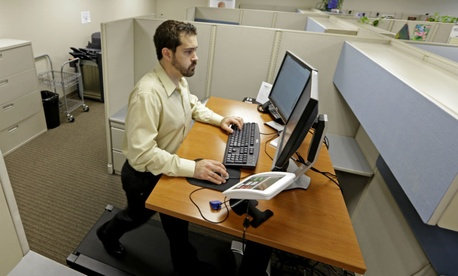 An employee works at a treadmill desk.