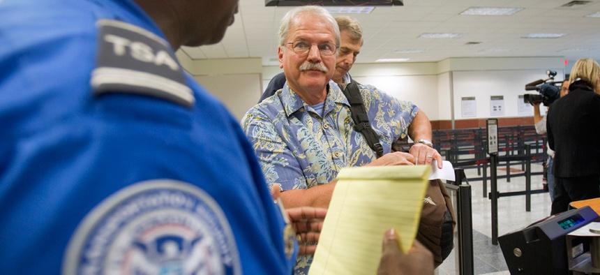 A TSA officer briefs a passenger in Atlanta in 2011.